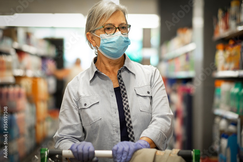 Fotomural Sad senior woman wearing face mask and rubber gloves pushes the shopping cart in