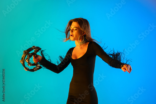 Canvas Print Caucasian female singer with tambourin isolated on blue studio background in neon light