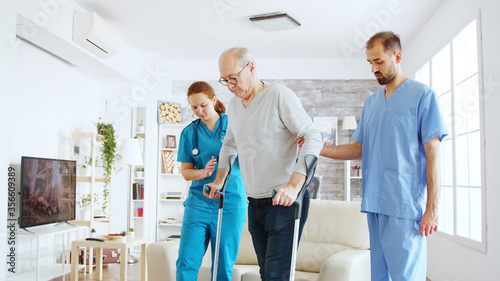 Fotografía Team of nurses or social workers helping an old disabled man to walk with his crutches out of the nursing home room