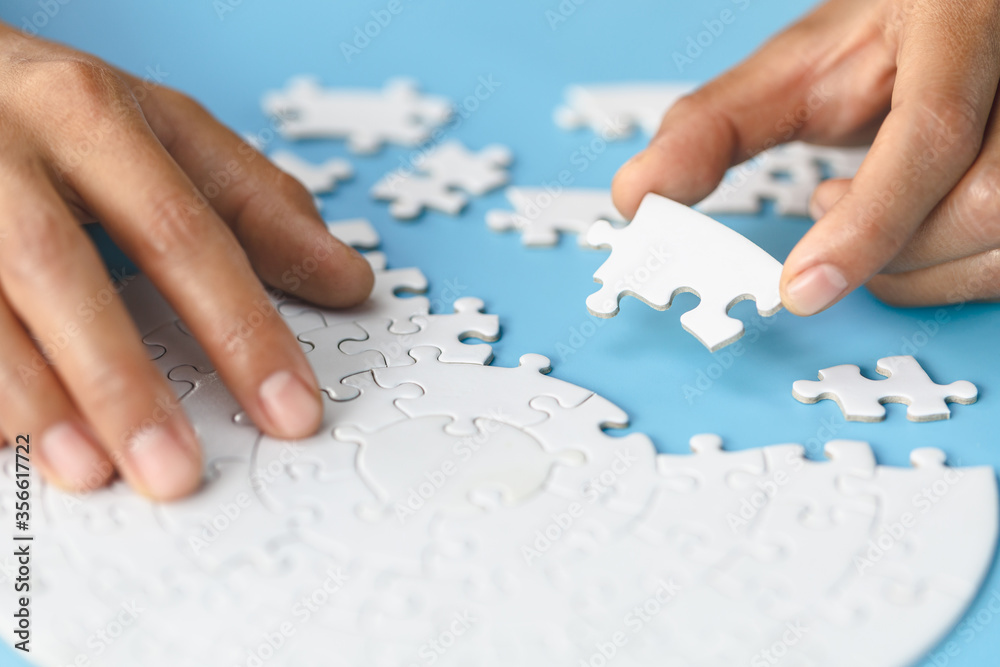 Fototapeta White jigsaw in the hands of humans, The correct solution. Teamwork, Solving and completing the task. Last piece of jigsaw puzzle. Assembling  jigsaw puzzle pieces.