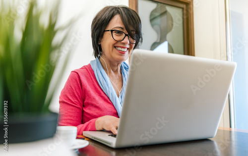Obraz Senior older woman working with laptop computer on the table at home indoor. Old mature people and technology concept - fototapety do salonu