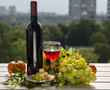 A glass and a bottle of red wine in nature. Summer alcoholic still life.