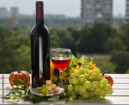 Fototapety, obrazy: A glass and a bottle of red wine in nature. Summer alcoholic still life.