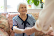 canvas print picture - Female home carer supporting old woman to stand up from the sofa at care home