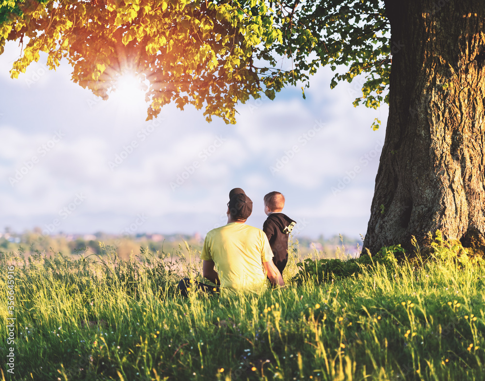 Fototapeta Dad with son in the spring meadow sitting under the tree in tall grass. Travel with child concept
