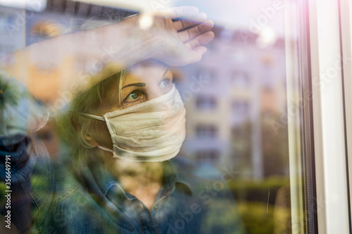 Obraz Senior woman looking out of window at home  - fototapety do salonu