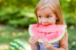 Child eating watermelon in the garden. Kids eat fruit outdoors. Healthy snack for children. 2 years old girl enjoying watermelon.