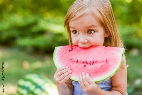 Photo Child eating watermelon in the garden