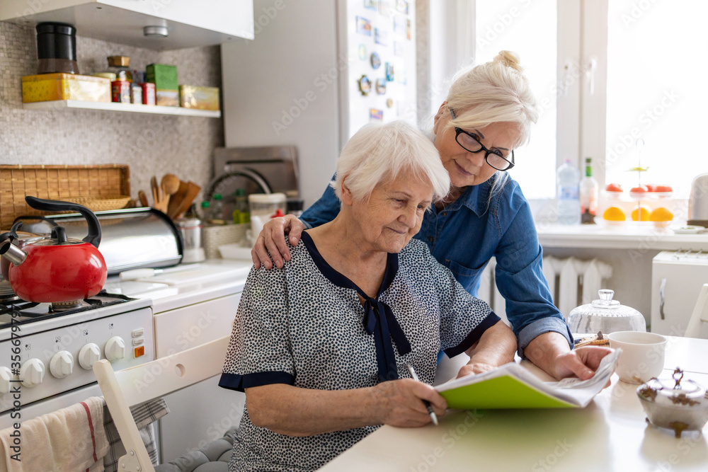 Fototapeta Mature woman helping elderly mother with paperwork