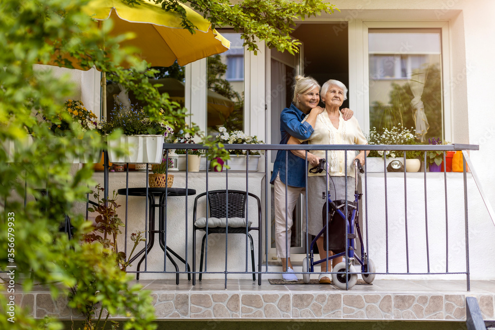 Fototapeta Senior woman and her adult daughter standing on balcony