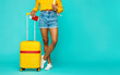 legs of a girl with a yellow suitcase on a blue background