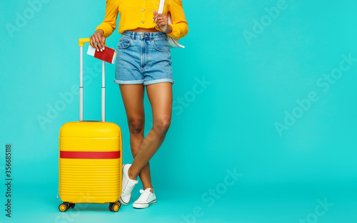 legs of a girl with a yellow suitcase on a blue background Canvas