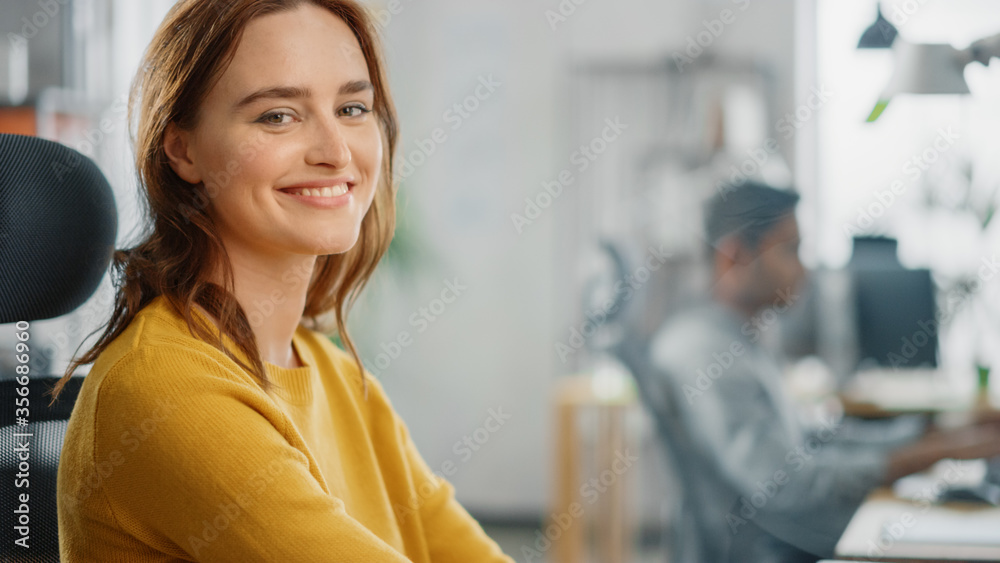 Fototapeta Portrait of Beautiful Young Woman with Red Hair Wearing Yellow Sweater Chats with Colleague and Turns Smilingly at Camera. Successful Woman Working in Bright Diverse Office.