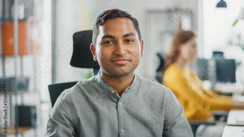 Fototapeta Portrait of Handsome Professional Indian Man Working at His Desk, Using Personal Computer and Smiling at the Camera