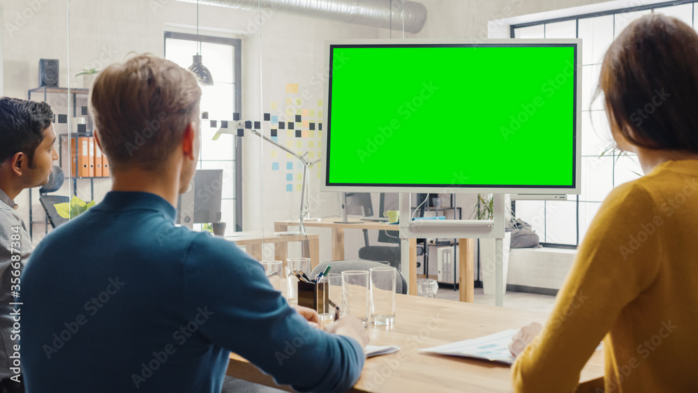 Fototapeta Team of Entrepreneurs Have a Meeting and Watch Green Screen Interactive Whiteboard. Young People Work in Creative Office.