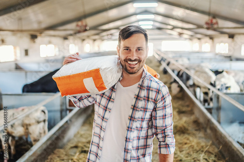 Young smiling attractive caucasian farmer standing in barn with sack with animal food over his shoulder and looking at camera Canvas Print