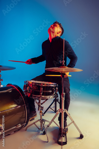 Photo Caucasian male drummer improvising isolated on blue studio background in neon light