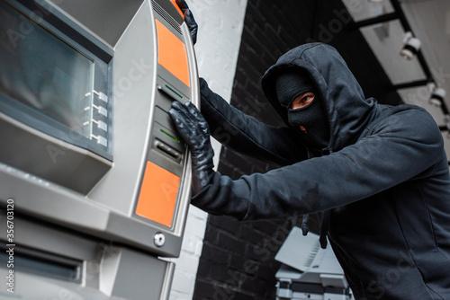 Valokuva Selective focus of burglar in mask pulling atm