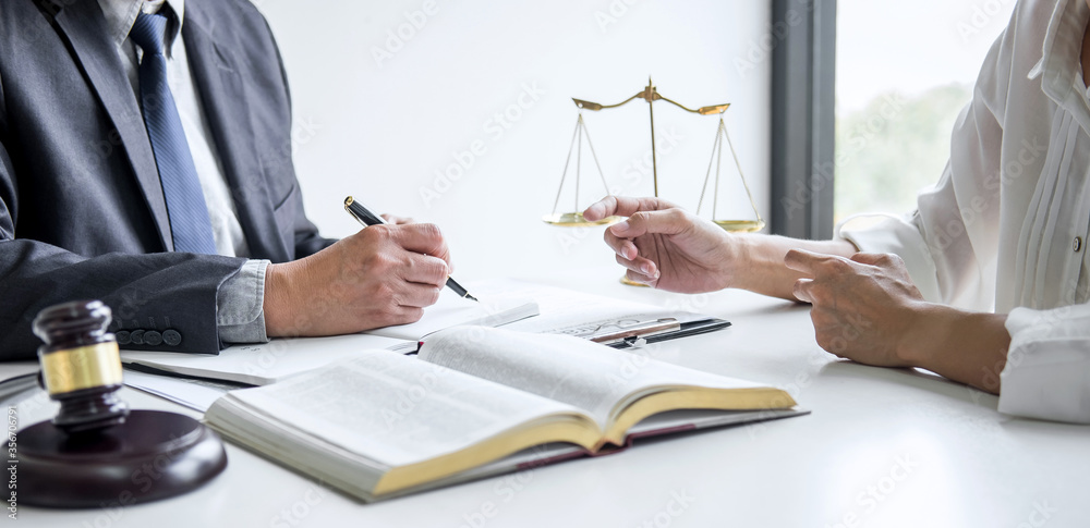 Fototapeta Businesswoman and Male lawyer or judge consult and conference having team meeting with client at law firm in office, Law and Legal services concept