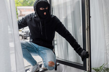 Selective Focus Of Robber In Balaclava Standing On Open Window
