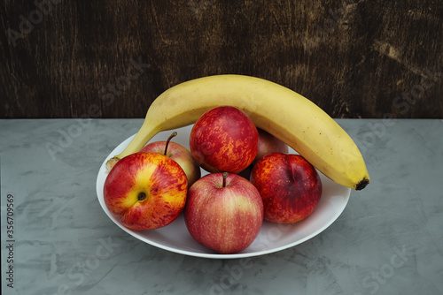 Fruit plate on a concrete base. Dark wooden background. View from above.