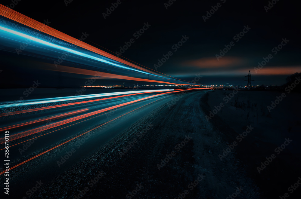 Fototapeta Long exposure of a road with light trails of passing vehicles, glowing sky