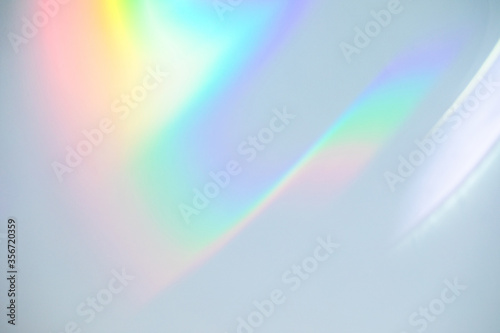 Obraz Blurred rainbow light refraction texture overlay effect for photo and mockups. Organic drop diagonal holographic flare on a white wall. Shadows for natural light effects - fototapety do salonu