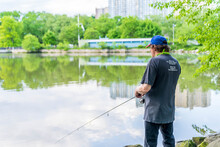 Manhattan, New York - May 30, 2020: Fisherman Casts His Line Off The Inwood Hill Park Shores.