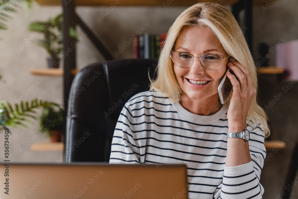 Fototapeta Smiling casual senior woman using laptop while talking on smartphone.