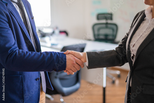 Fototapeta Handshake of unrecognizable business persons as a gesture of a successful deal. Hands of office workers in suits during a greeting. Partnership agreement. Faceless managers. obraz