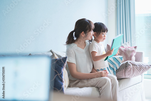 Fotografía ソファに座って絵本を読む親子