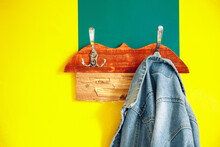 Colorful Interior Wall Vintage Simple Style Furniture Background Object With Jeans Jacket On A Wooden Hanger Bright Yellow And Green Painted Surface With Empty Copy Space For Your Text
