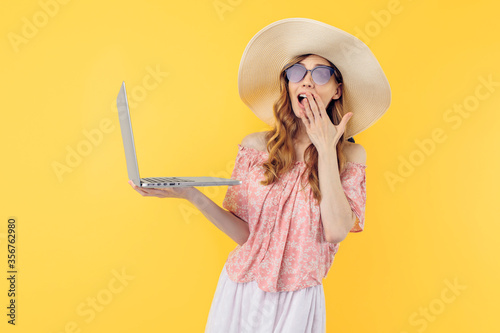 Shocked surprised a beautiful woman in a straw hat and sunglasses uses a laptop Canvas Print