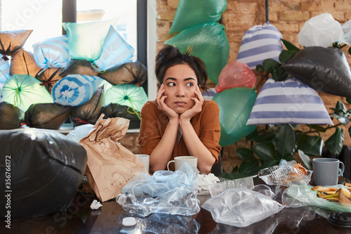 Obraz na plátně Asian woman spending time at her apartment full of rubbish