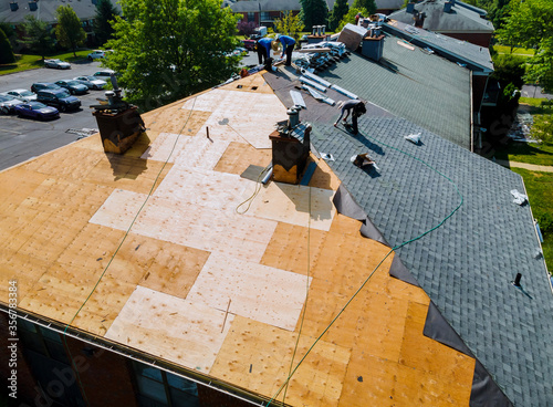 Obraz Roof repairs old roof replacement with new shingles of an apartment - fototapety do salonu