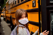 Child Wearing A Facemask By School Bus. A Girl With A Face Mask Is Boarding A School Bus.