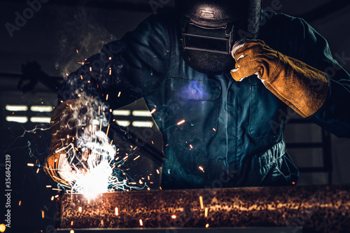 Fotografija Metal welder working with arc welding machine to weld steel at factory while wearing safety equipment