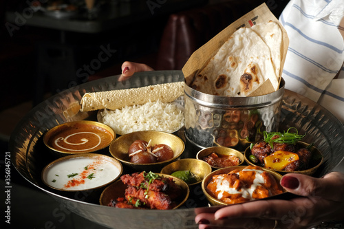 Obraz na plátně A lady holding an Indian Thali with Rice, Curry, Gravy, Bread, Pickles and Sweet