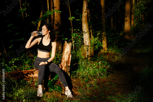 Photo A young girl drinks mineral water while sitting on a log in the forest
