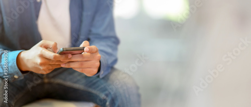 Fotografía A man using smartphone while sitting on sofa at hotel lobby with blurred backgro