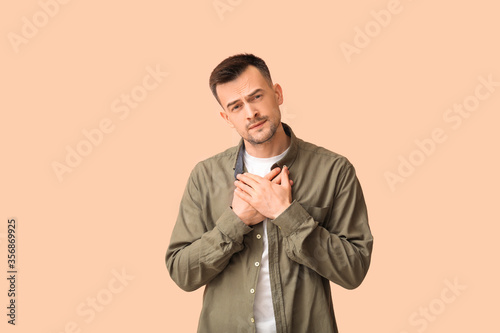 Photo Portrait of apologizing man on color background