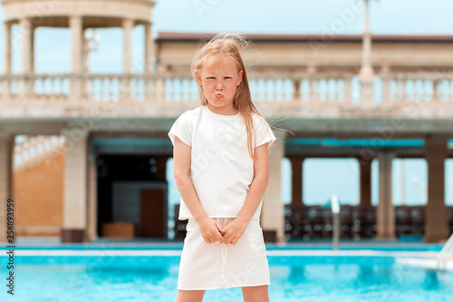 Portrait of a sad little girl standing by the pool Canvas-taulu