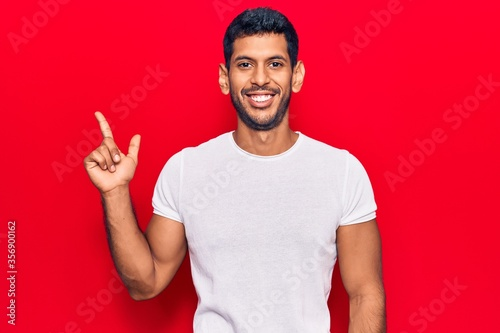 Obraz Young latin man wearing casual clothes smiling happy pointing with hand and finger to the side - fototapety do salonu