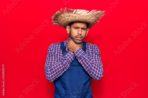 Photo Young latin man wearing farmer hat and apron shouting and suffocate because painful strangle
