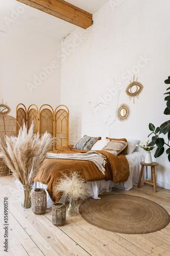 Fototapeta Comfort bedroom in boho style interior with lovely furnishing obraz