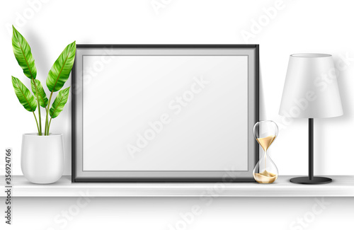 Empty photo frame stand on white shelf with potted plant, hourglass and table lamp, home interior decor with blank place for picture and black border Canvas Print