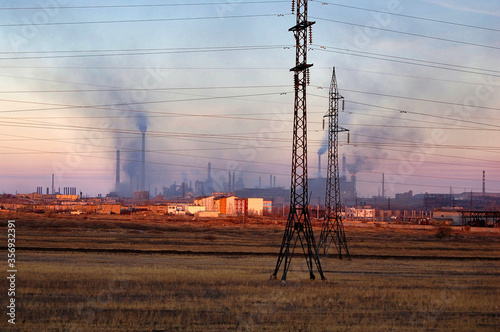 Obraz na plátne Smoke stacks and chimneys belching smoke above the Temirtau steel works in central Kazakhstan at sunset