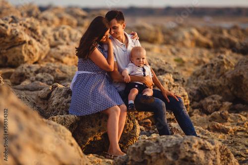 Obraz Mom, dad and son. The family strolls along the stony beach by the sea. - fototapety do salonu