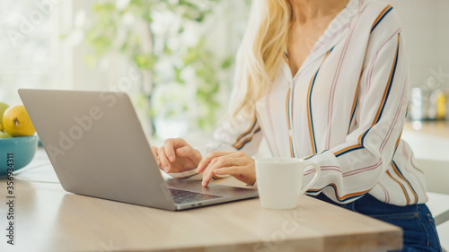 Vászonkép Close Up on Hands of a Woman Using Laptop Computer and Drinking Morning Cup of Coffee or Tea