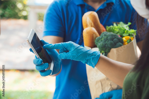 Woman appending signature in digital mobile phone after Grocery store delivery man wearing blue shirt delivering food to a woman at home Canvas Print